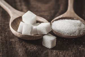 sugar cubes and cane in wooden spoon