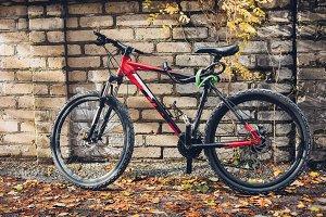 Red Mountain Bike Stands Near A Bric