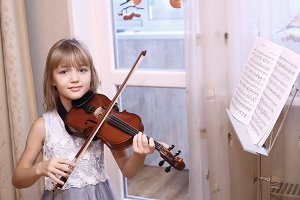blond preteen girl playing violin