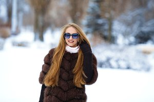 Beautiful smiling girl in a fur coat