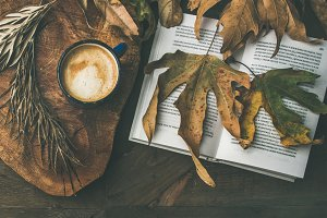 Fall morning coffee concept with fallen leaves, jamper and book