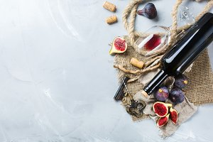 Bottle, corkscrew, glass of red wine, figs on a table