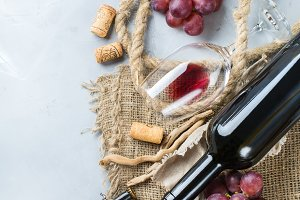 Bottle, corkscrew, glass of red wine, grapes on a table