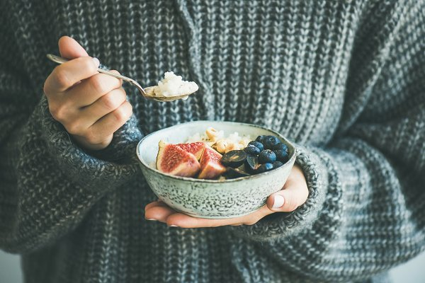 Woman in woolen sweater eating rice…