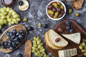 snacks of blue cheese, olives, bread and grapes