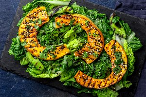 Grilled pumpkin and lettuche salad with white and black sesame and balsamic sauce on slate black board, blue stone background