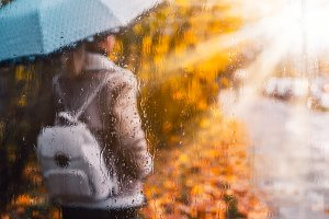 Golden autumn season. Watercolor like blurred blond girl with backpack and bright umbrella stands under rainy drops and droplets. Backlit sunset sun flares shining. Wet gray ground