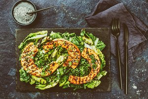 Grilled pumpkin and lettuche salad with white and black sesame and balsamic sauce on slate black board, blue stone background. Toned photography