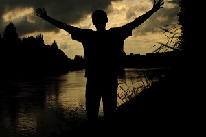 silhouette man arms raised sunset sky landscape
