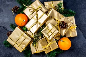 Christmas background. Golden gift boxes and Christmas decoration - oranges, Christmas tree branches and cones on slate background. Flat lay, top view