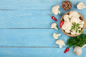 Fresh cauliflower with garlic and chili peppers on blue wooden background with copy space for your text. Top view