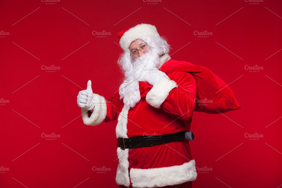 christmas santa claus with big bag on shoulder is on red background