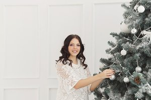 Teen girl decorates Christmas tree