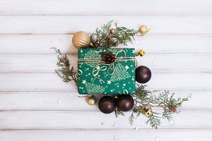 Christmas gift box and christmas tree and ball toy and cone on white wooden vintage background