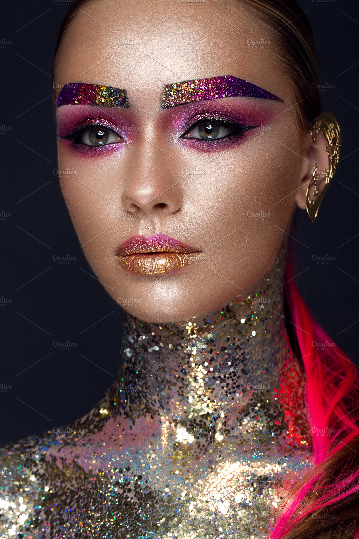 66de2b9d443cd Beautiful girl with creative glitter makeup, sparkles, unusual eyebrows.  Beauty is an art face.