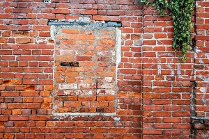 The brick wall, the window is bricked, the old cement red brick in the summer in the city, a building that is abandoned.