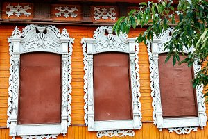 A beautiful wooden window with a pattern of bright orange background, a closed window with metal planks. In the summer in an abandoned city in the fall.