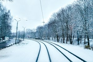 White snow in city on a tramway in November, first snow December. Snow-covered city with trees in winter. Rails sleepers turning into the distance.
