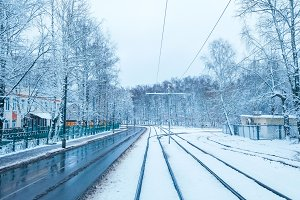 White snow in the city on a tramway in November, the first snow in December. Snow-covered city with trees in winter. Rails sleepers turning into the distance.