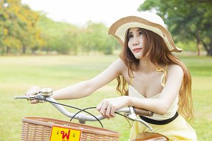 Asian woman sitting on a bicycle