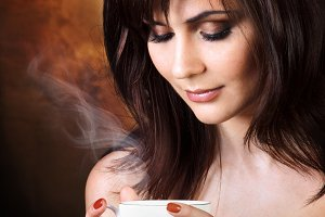 Beautiful girl enjoys aroma of coffe