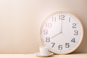 Steaming coffee cup and clock