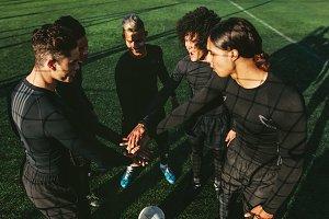Soccer team stacking hands