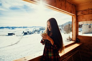 girl drinks tea on winter terrace