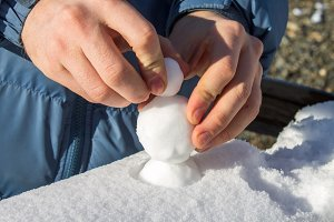 Male hands sculpting from the snow small snowballs that would make a snowman.