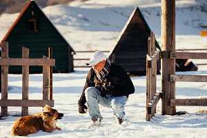 man play with dog in snowy winter