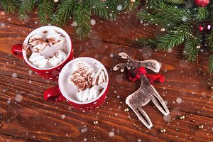 Christmas hot chocolate with marshmelow on a dark wooden background, christmas tree branches decorating.