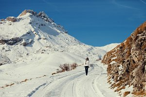 woman walk in snowy road in mountain