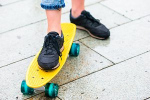 Hipster girls with skateboard outdoors in the rain. Closeup skatebord. Active sporty woman having fun in skate park.