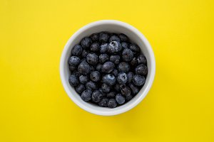 Bowl of blueberries on yellow