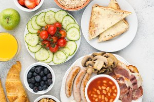 Full English breakfast, eggs, bacon, sausages, breads and fruits