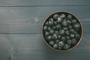 Blueberries fruit on bowl on wood