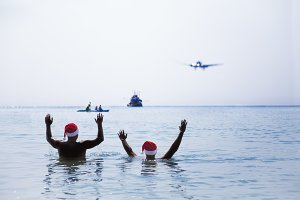 Two men in Santa Claus red hat greet salute airplane in morning
