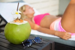 Coconut juice drink with woman on lounger near a swimming pool