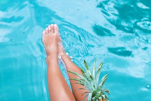 Slim woman holding pineapple fruit near swimming pool tropical exotic concept