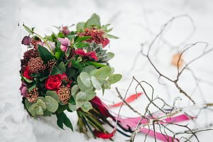 Beautiful wedding bouquet with succulents, greenery and crimson flowers on the snow. Outdoors. Artwork