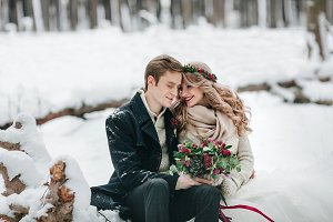 Cute couple in love with a bouquet are sitting on the log on background of the winter forest. Artwork
