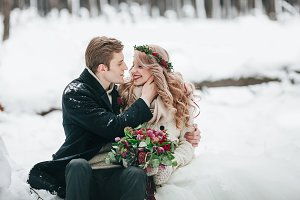Couple in love with a bouquet are sitting on the log on background of the snowy forest. Winter wedding. Artwork