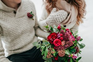 Bride and groom in warm winter clothes holds in hands a rustic wedding bouquet with red and crimson flowers. Close-up.