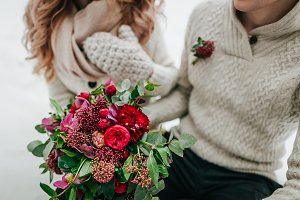 Wedding bouquet with red and crimson flowers on blurred bride and groom background. Winter wedding outdoors