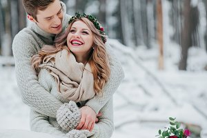Bride and groom are hugging in the winter forest. Couple in love. Winter wedding ceremony.