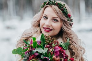 Face of a smiling girl of Slavic appearance with a wreath. Beautiful bride holds a bouquet in winter background.