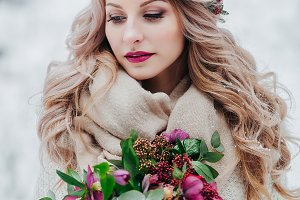 A young girl of Slavic appearance with a wreath of wildflowers. Beautiful bride holds a bouquet in winter backgrou