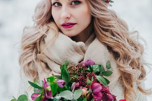 A young girl of Slavic appearance with a wreath of wildflowers. Beautiful bride holds a bouquet in winter background.
