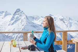 Woman snowboarder drinking water.