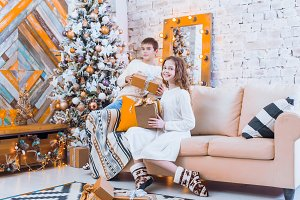 Two children a boy and a girl at a Christmas tree on a sofa with
